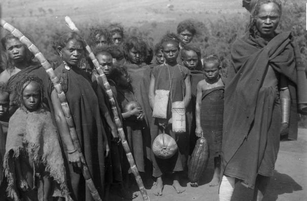 """Sekelompok perempuan dan anak-anak dari Badjawa, sebagian perempuan sedang memegang potongan-potongan tebu. Di sebelah kiri mereka adalah """"teman mereka, Tai Ngade, kepala Kampung Menge di lereng sebelah timur Inije Lika (onderafdeling Ngada, di Flores Tengah), mengenakan satu set besar cincin tembaga pada lengan kiri dan kaki kanan. Foto diambil oleh G.P. Rouffaer pada 22 Juli 1910, yang berarti sekitar 20-an tahun sebelum Gerson Poyk tinggal di Bajawa. [Credit foto: KITLV]"""