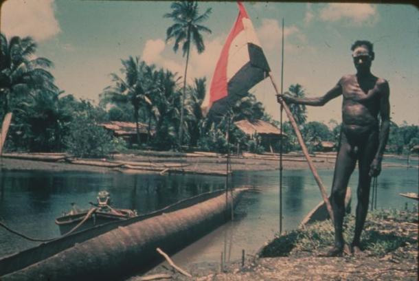 Seorang laki-laki Asmat dengan bendera Belanda. Tahun tidak diketahui. [Sumber: www.papuaerfgoed.org]