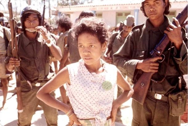 """Elemen sipil dan bersenjata selama kudeta UDT di bulan Agustus 1975, nampak seorang perempuan dengan tulisan di dada berbunyi: """"""""Women are on the move.'[Archives & Museum of East Timorese Resistance]"""