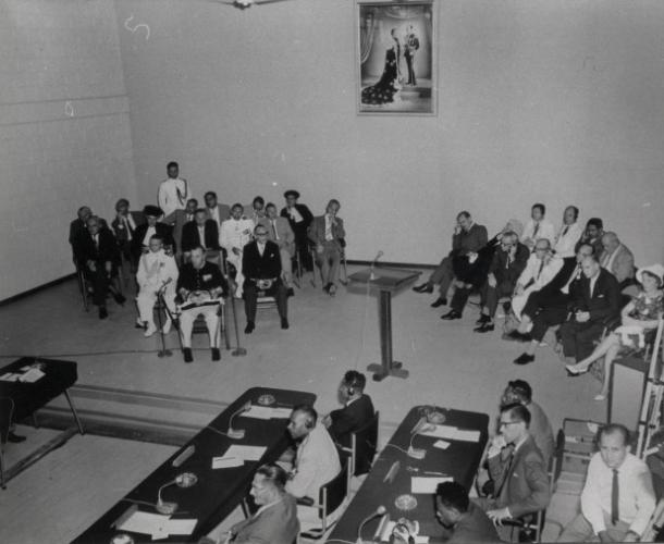 Pembukaan de Nieuw-Guinea Raad atau Dewan Guinea-Baru, di belakang meja dari kanan, depan ke belakang, Wakil ketua Kedua Nicolaas Jouwe, presiden JHF Sollewijn Gelpke dan wakil ketua pertama Markus Wonggor Kasiepo, dan lebih lanjut ke sudut kiri depan Gubernur P.J. Platteel, dan di sudut kanan di barisan depan dalam kostum terang Menteri EH Toxopeus (kedua dari kanan) dan Sekretaris Th.H. Bone, dengan sampingnya pemimpin delegasi, Ny JM Stoffels van Haaften dan delegasi dari Australia dan Selandia Baru. [Sumber: KITLV]